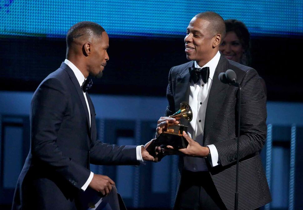 Jamie Foxx, left, presents Jay-Z with the award for best rap/sung collaboration at the 56th annual Grammy Awards. (Matt Sayles / The Associated Press)