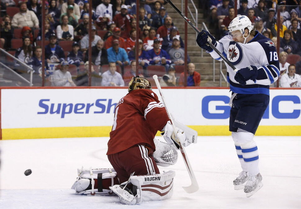 Winnipeg Jets' Bryan Little (18) tries to redirect the puck in front of Phoenix Coyotes' Thomas Greiss, left. (Ross D. Franklin / The Associated Press )