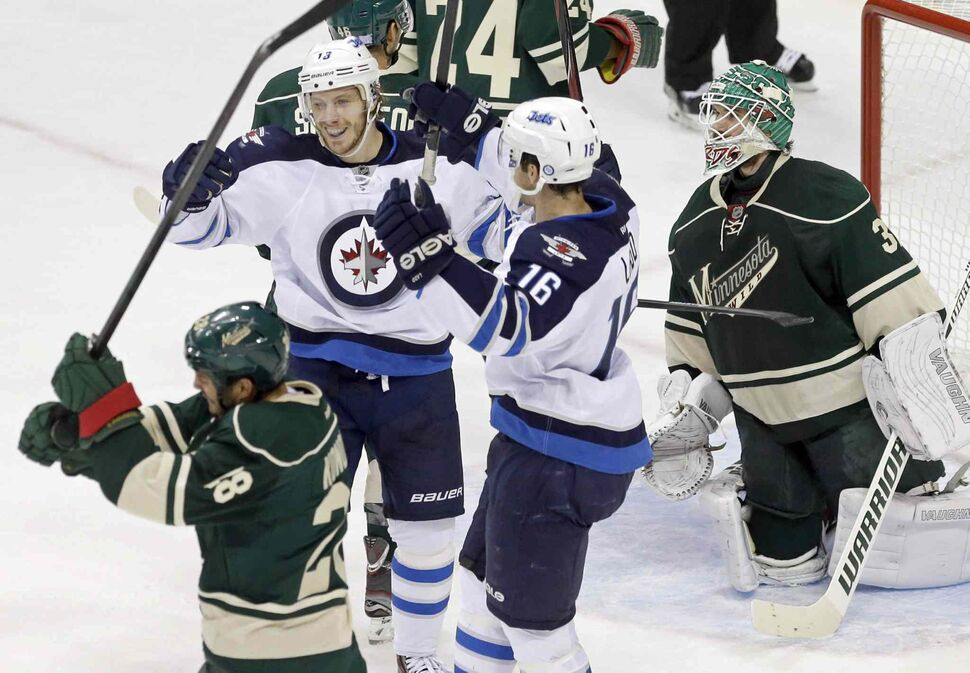 Bryan Little (18) and Andrew Ladd (16) celebrate Little's first-period power-play goal off Minnesota Wild goalie Josh Harding (right), as Zenon Konopka (lower left) swings his stick toward the ice in frustration. (Jim Mone / The Associated Press)