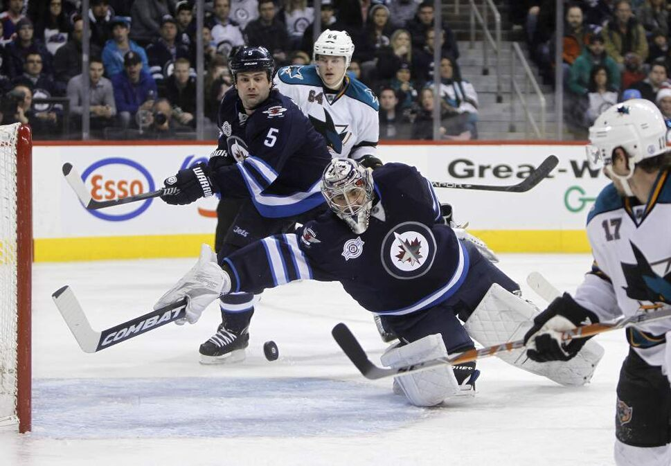 Winnipeg Jets' goaltender Ondrej Pavelec (31) makes a miraculous paddle save against the San Jose Sharks' early in the third period of NHL action at MTS Centre, January 12, 2011. Winnipeg Jets' Mark Stuart (5) and San Jose Sharks' Jamie McGinn (64) look on behind him. (TREVOR HAGAN/WINNIPEG FREE PRESS)