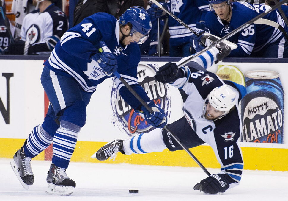 Toronto Maple Leafs forward Nikolai Kulemin (41) takes out Winnipeg Jets forward Andrew Ladd (16) during the second period. (Nathan Denette / The Canadian Press)