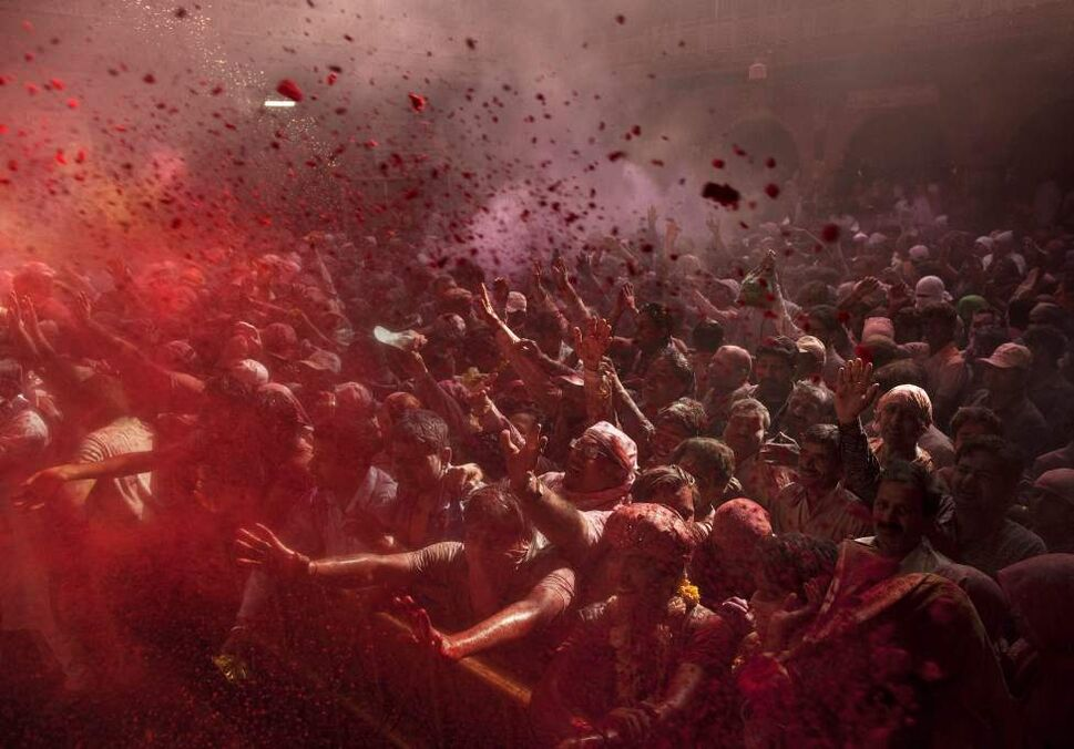 "Hindu devotees pray and face a deity as colored powder is thrown on them while celebrating ""Holi,"" the festival of color, crowd at the Banke Bihari temple in Vrindavan, about 140 kilometers (87 miles) from New Delhi, India, Wednesday, March 7, 2012. Vrindavan is a famous place for Holi celebrations, where according to legend, the Hindu god Krishna played Holi with his consort Radha. (AP Photo/Kevin Frayer) (CP)"