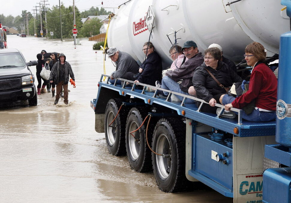 Residents ride on the side of a tanker truck as their homes are evacuated in High River, Alta. (Jeff McIntosh / The Canadian Press)