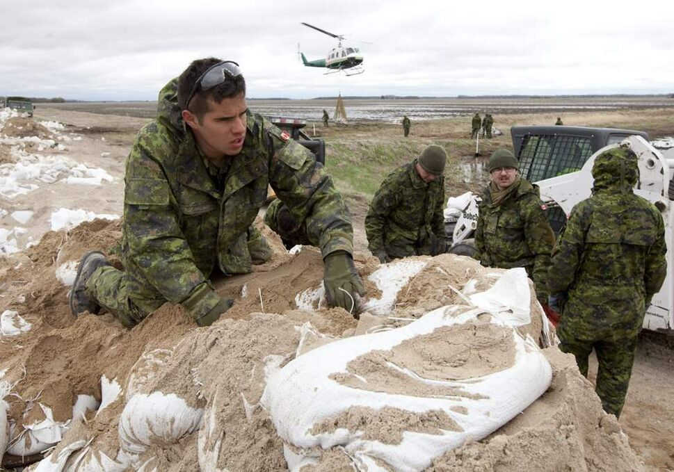 Members of 2nd battalion Princess Patricia's Light Infantry help load sandbags onto helicopter slings to be transported to weak sections of the dike running along the Assiniboine River some 25km from Portage La Prairie, Man. Thursday, May 12, 2011.   (THE CANADIAN PRESS/Jonathan Hayward)