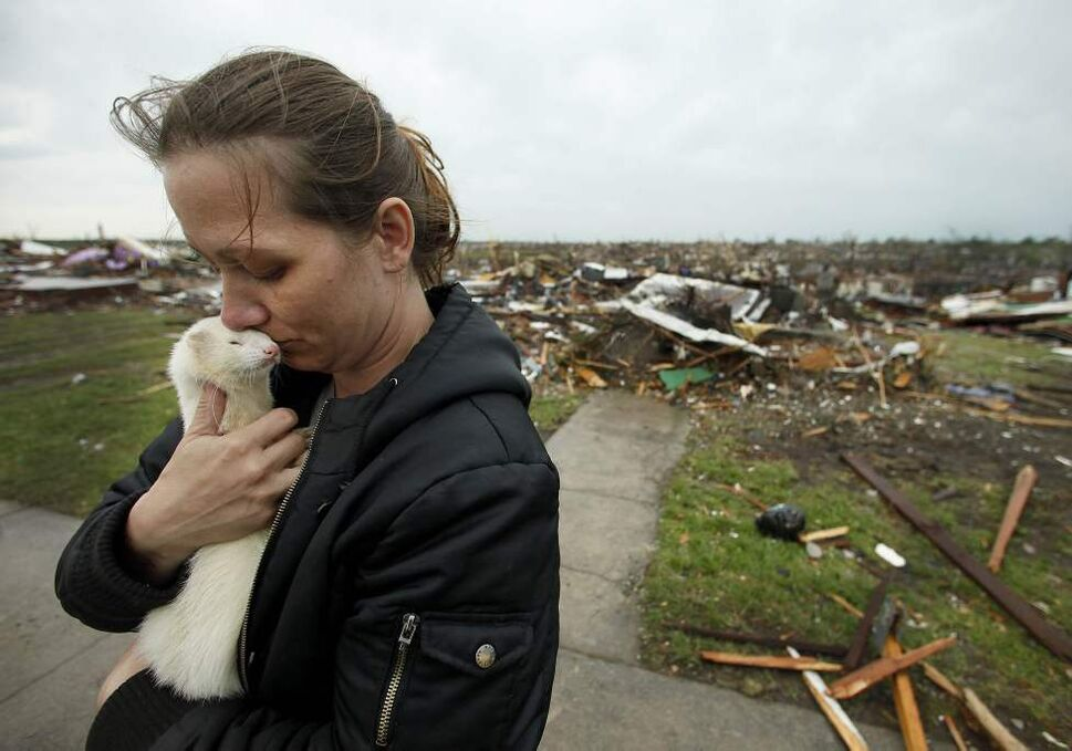 Ashley Stephens holds a ferret she rescued from the home of a missing woman while helping a friend collect belongings Monday, May 23, 2011, in Joplin, Mo.  (AP Photo/Charlie Riedel) (CP)