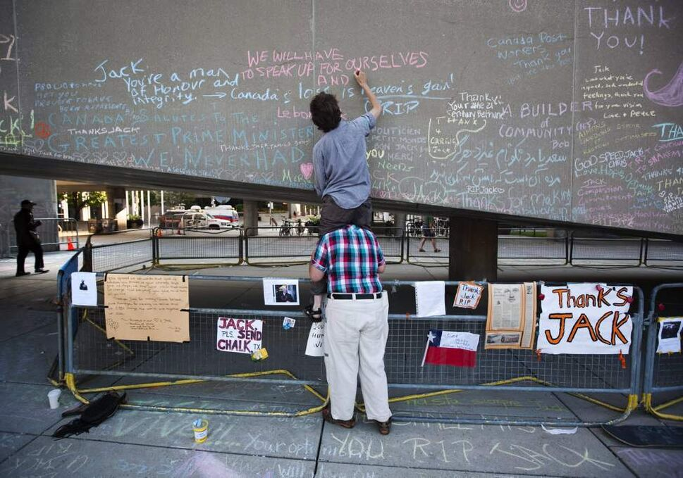 Mary Daniel sits on the shoulders of Marc Cannon to write a message of condolence in chalk at Nathan Phillips Square prior to the funeral of the late NDP leader Jack Layton in Toronto on Saturday, August 27, 2011. THE CANADIAN PRESS/Darren Calabrese