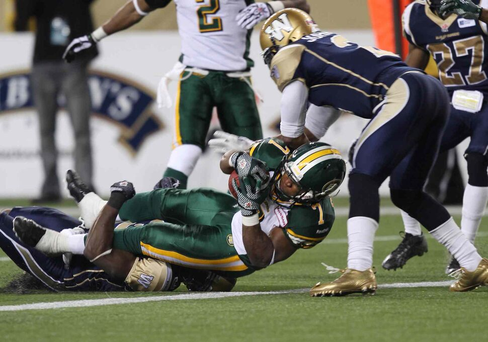 Winnipeg Blue Bombers Cauchy Muamba (bottom) and Jovon Johnson try unsuccessfully to hold back Edmonton Eskimos' Hugh Charles as he pounds in for a touchdown in overtime. the Esks added a two-point convert. (Joe Bryksa / Winnipeg Free Press)