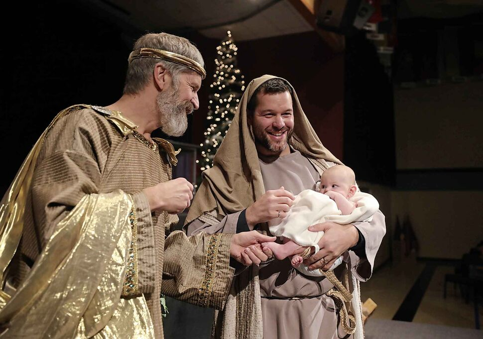 John Kachuro holds his daughter, 4-month-old Brielle Kachuro, who is playing baby Jesus, and chats with Ken Peters who plays King Harrod after rehearsing the nativity scene at Gateway Church on Dec. 21.  (Ruth Bonneville / Winnipeg Free Press)