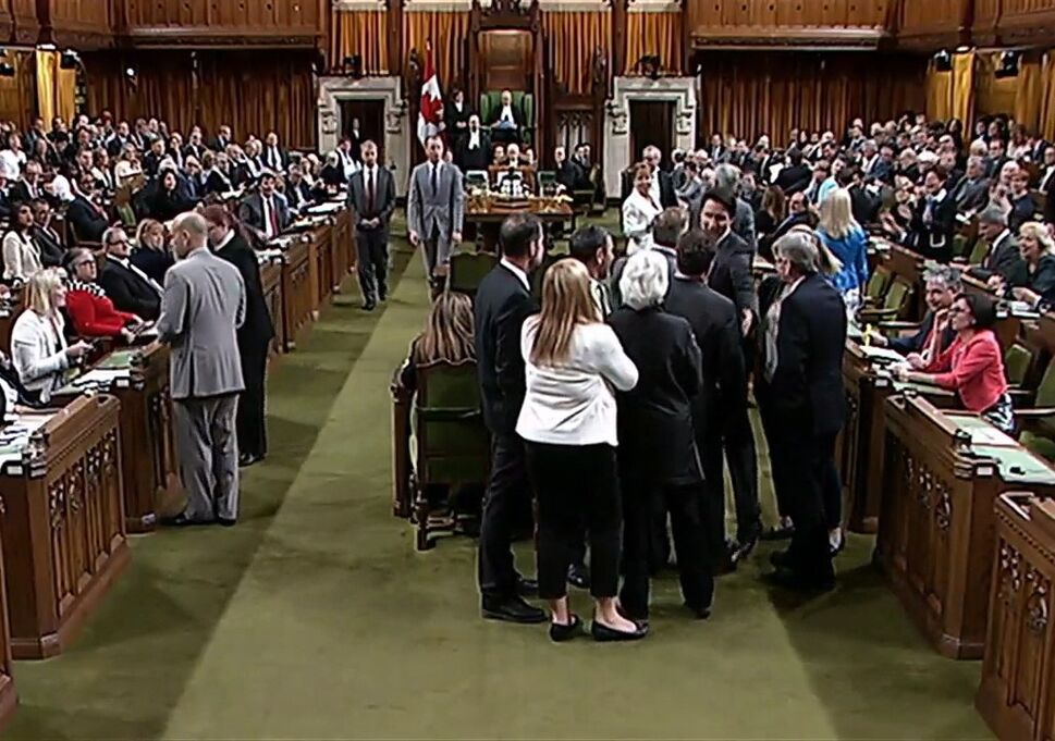 Canadian Prime Minister Justin Trudeau, facing towards the camera left of centre of the frame, is shown near Opposition whip Gordon Brown in the House of Commons in Ottawa on Wednesday. Footage from the Commons television feed shows Trudeau wading into a clutch of MPs, mostly New Democrats, and pulling Opposition whip Gordon Brown through the crowd in order to get a vote started. (HO-House of Commons / THE CANADIAN PRESS)