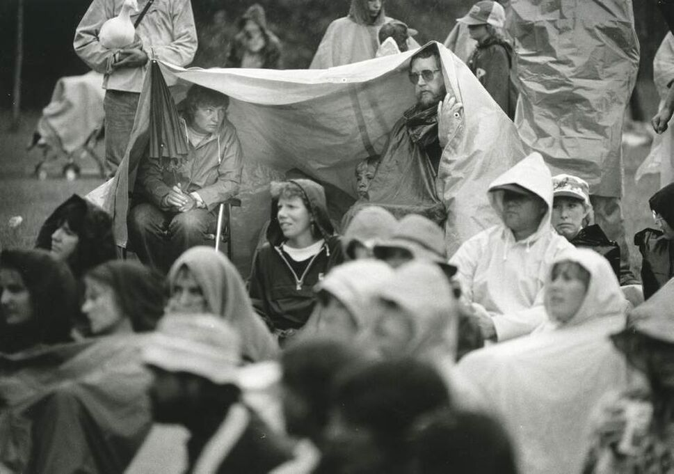 Folks (left to right) Sandy Anderson and husband Gene, from Frazee, Minnesota, keep dry beneath a canvas during a downpour at the 1984 Winnipeg Folk Festival, while son Mitch sits on the ground at centre. (KEN GIGLIOTTI / WINNIPEG FREE PRESS)