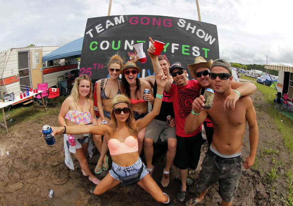 "Friday afternoon party in the campground. This group brought a sign stating their name as ""Team Gong Show.""  (BORIS MINKEVICH / WINNIPEG FREE PRESS )"