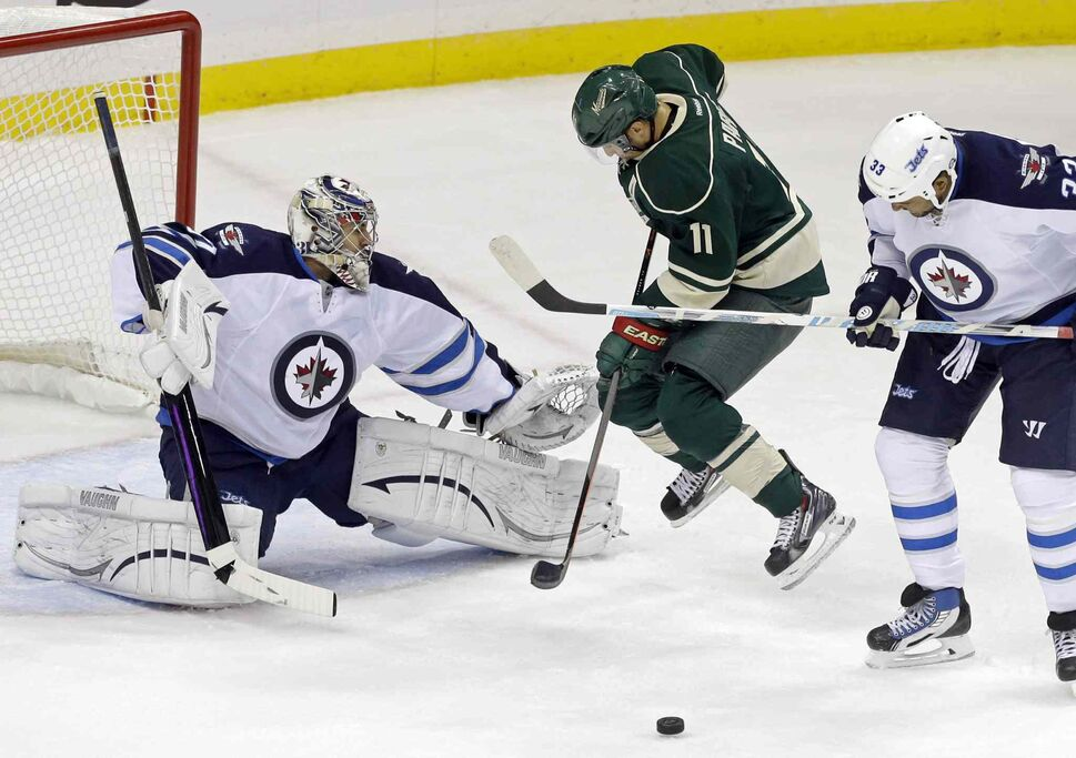 Zach Parise (centre) of the Minnesota Wild jumps clear of a first-period shot stopped by Winnipeg Jets goalie Ondrej Pavelec (left), as Jets' Dustin Byfuglien looks on. (Jim Mone / The Associated Press)