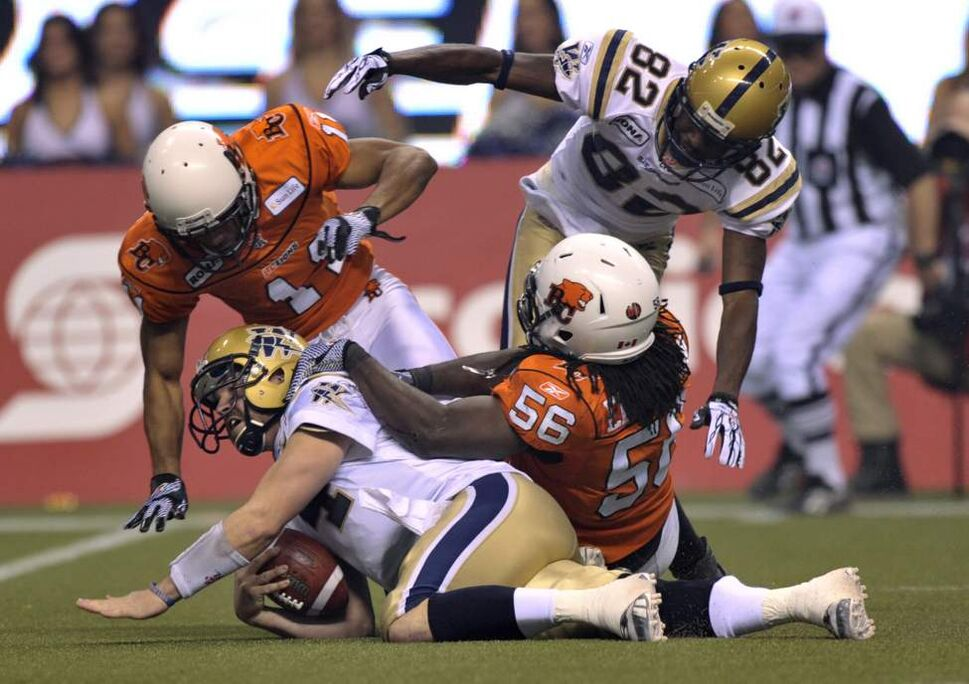 Winnipeg Blue Bombers quarterback Buck Pierce is taken down by B.C. Lions defensive back Tad Kornegay, left, and linebacker Solomon Elimimian during third quarter of the 99th CFL Grey Cup.