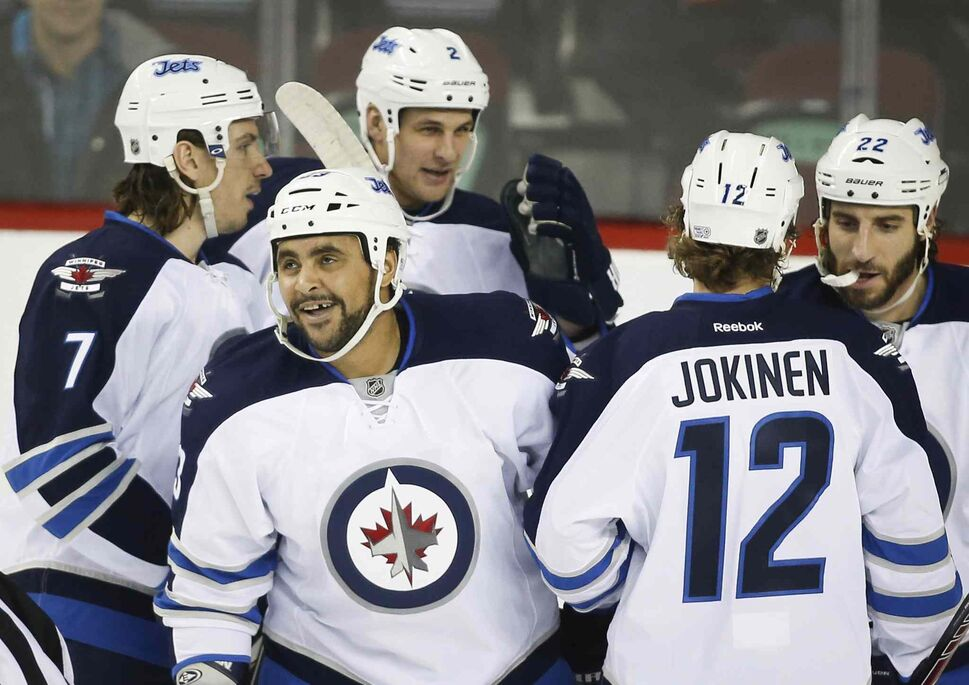 Winnipeg Jets' Dustin Byfuglien, second from left, celebrates his goal with teammates during the first period against the Calgary Flames in Calgary. (Jeff McIntosh / The Canadian Press)