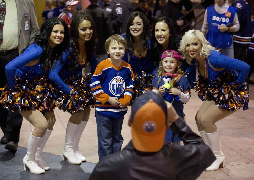 Edmonton Oilers fans get their photo taken with the Oilers cheerleaders Tuesday. The Edmonton Oilers took on the Winnipeg Jets in their home opener. (Jason Franson / The Canadian Press)