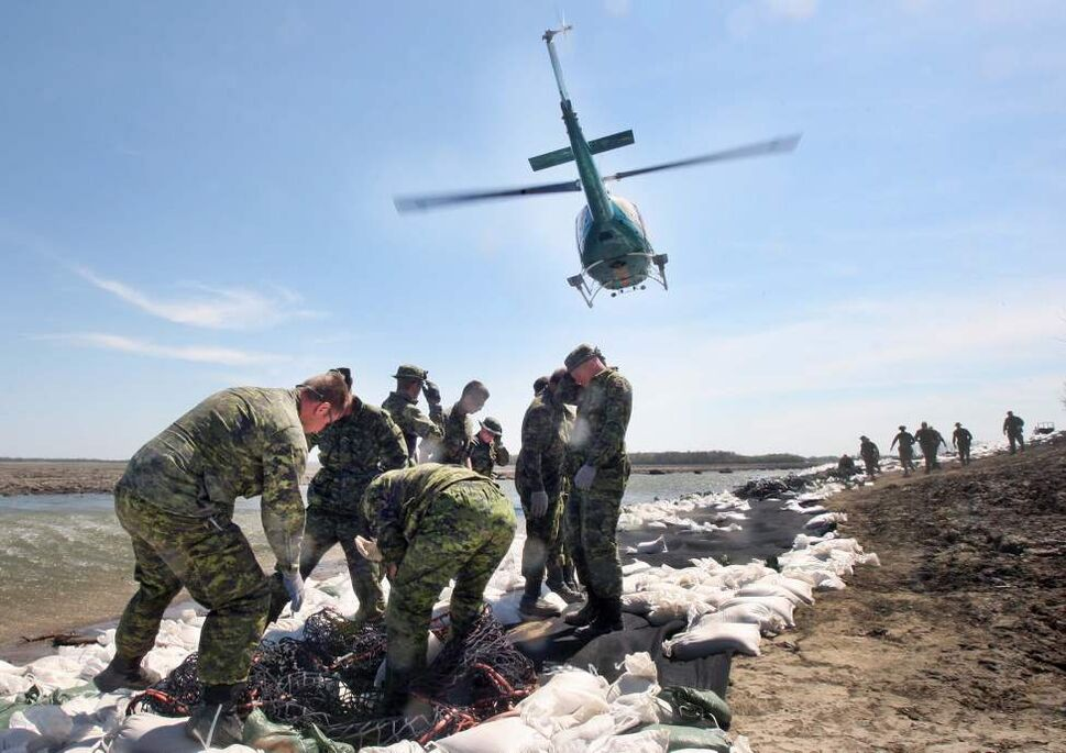 Near Hwy 430- North of the Trans Canada Hwy -  Members from 2 PPCLI , and 1st Regiment Royal Canadian Horse Artillery from Shilo, shield themselves from sand flying off a helicopter that dropped off sandbags needed to shore up a soft dike on the Assiniboine River Tuesday afternoon.