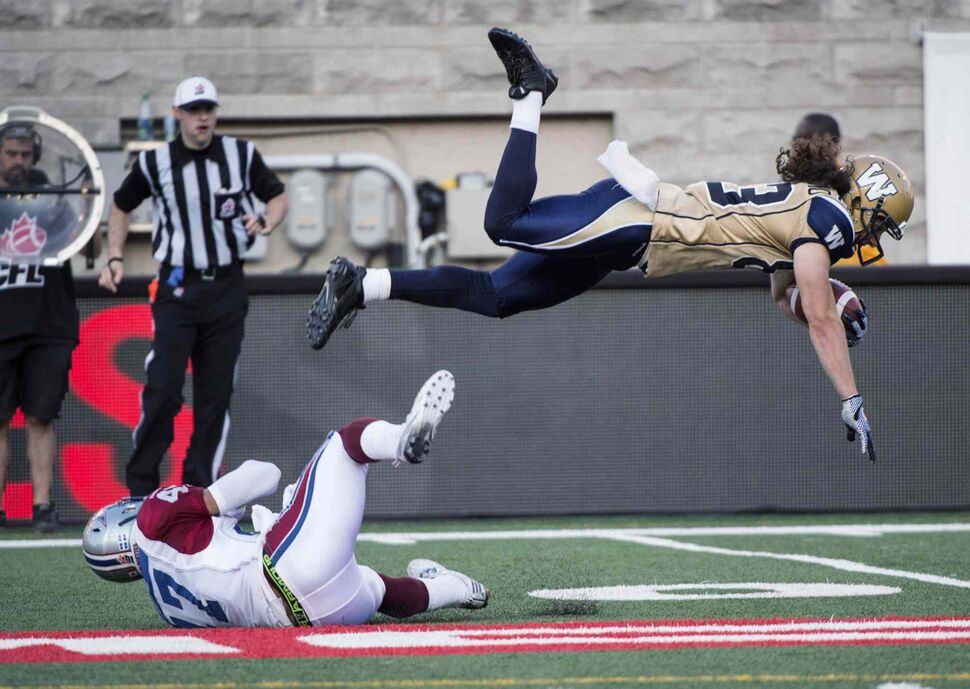 Winnipeg Blue Bombers' wide receiver Julian Feoli-Gudino flies over Montreal Alouettes' defensive back Jamaan Webb during first quarter CFL football action Friday, July 11, 2014 in Montreal.  (Paul Chiasson / The Canadian Press)