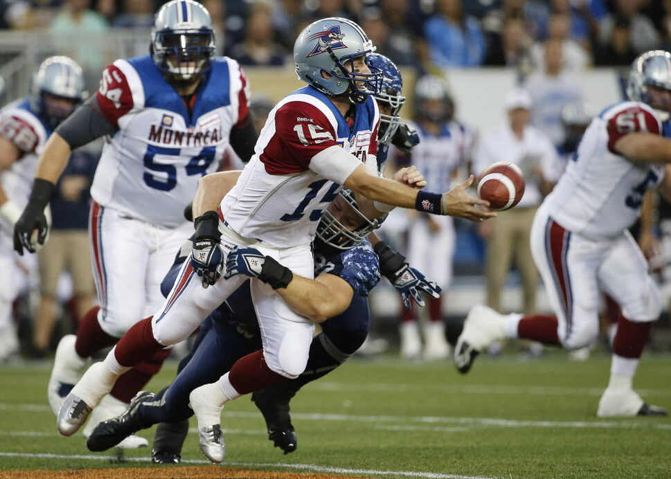 Montreal Alouettes' quarterback Alex Brink (15) tosses the ball out as he gets taken down by Winnipeg Blue Bombers' Greg Peach (90). (John Woods / The Canadian Press)