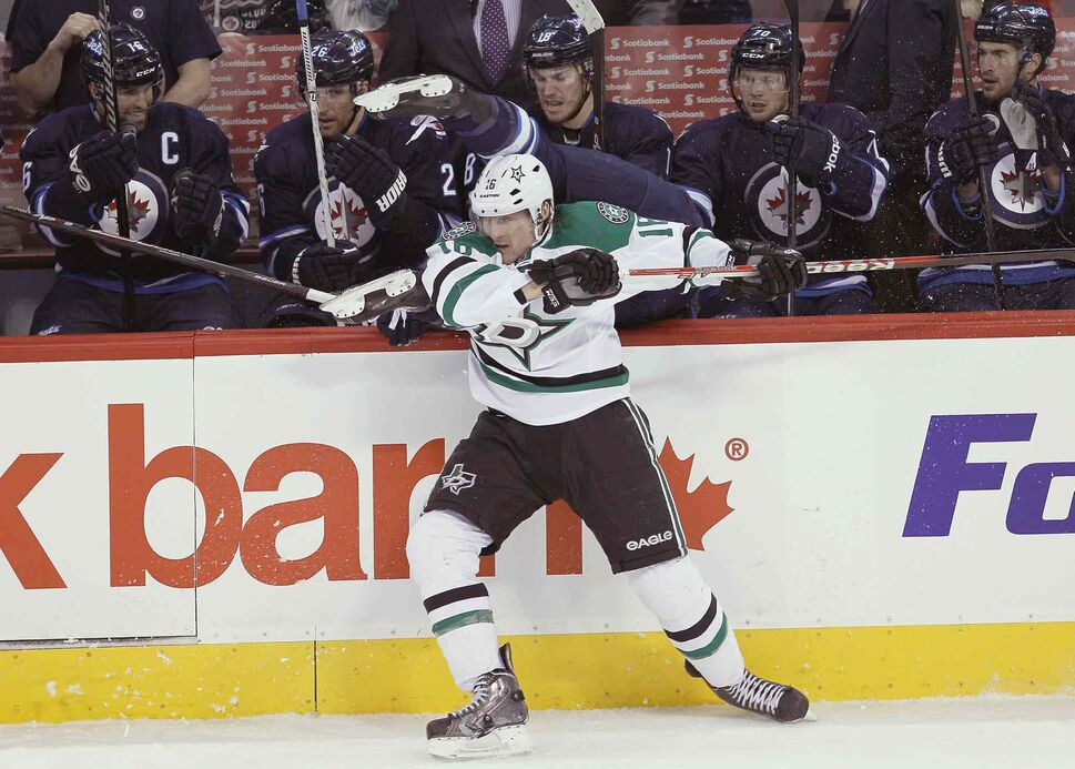Ryan Garbutt (bottom) of the Dallas Stars checks Mark Scheifele of the Winnipeg Jets over the boards during the first period. (JOHN WOODS / THE CANADIAN PRESS)