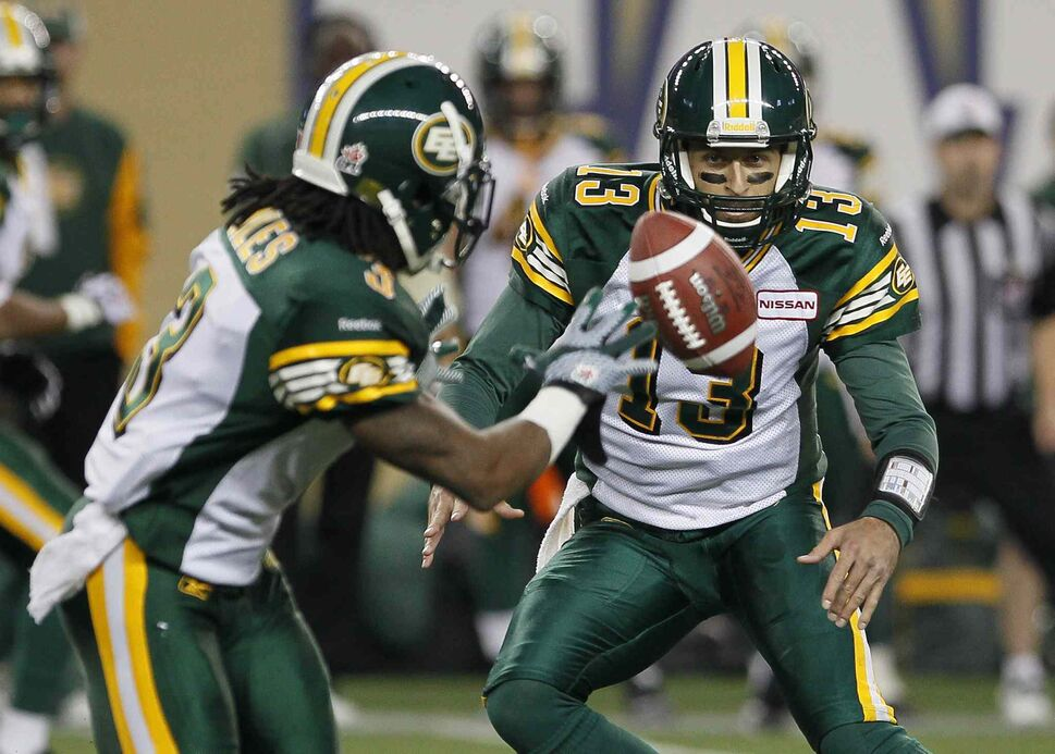 Edmonton Eskimos' quarterback Mike Reilly (right) tosses out to Jamal Miles during the first half. (John Woods / The Canadian Press)