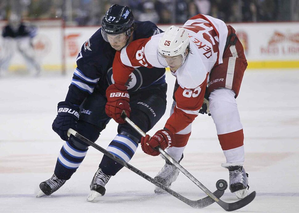Winnipeg Jets forward Eric Tangradi fights for the puck with Detroit Red Wings forward Danny DeKeyser in the second period. (JOHN WOODS / THE CANADIAN PRESS)
