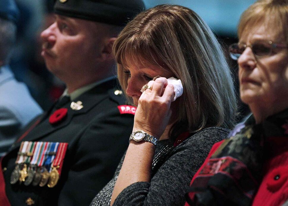 A woman weeps during a Remembrance Day service at the RBC Convention Centre Winnipeg on Tuesday, Nov. 11, 2013. (JOHN WOODS / THE CANADIAN PRESS)