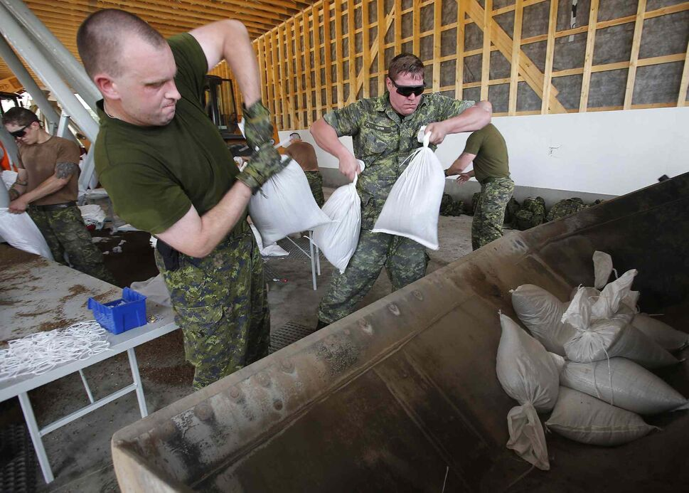 Military from Shilo fill and load sandbags in Portage La Prairie, Man. Saturday. (John Woods / The Canadian Press)