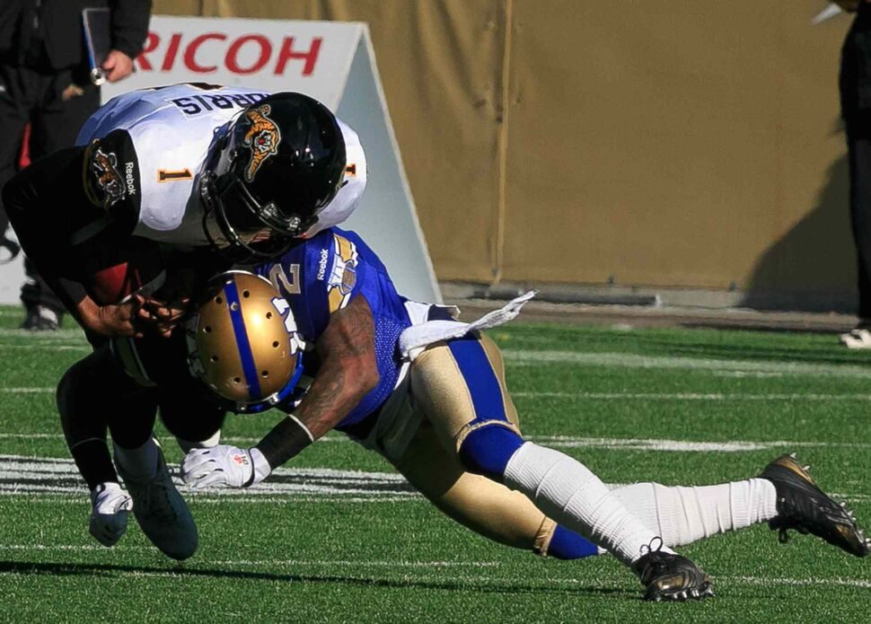 Ticats' quarterback Henry Burris is taken down by Jovon Johnson in the first quarter. (Melissa Tait / Winnipeg Free Press)