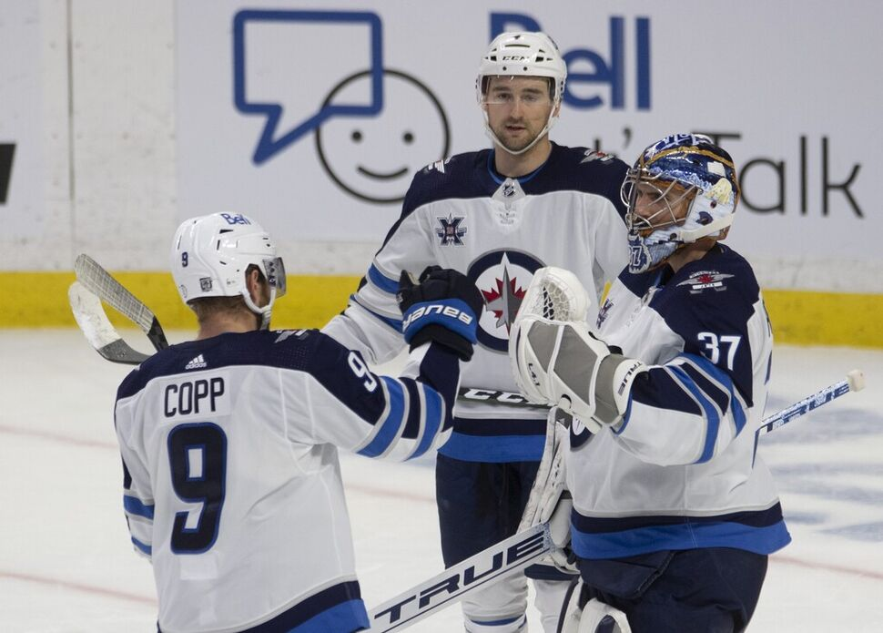 Andrew Copp, Neal Pionk and goaltender Connor Hellebuyck celebrate after the Winnipeg Jets beat the Ottawa Senators on Thursday. (Adrian Wyld / The Canadian Press) (CP)