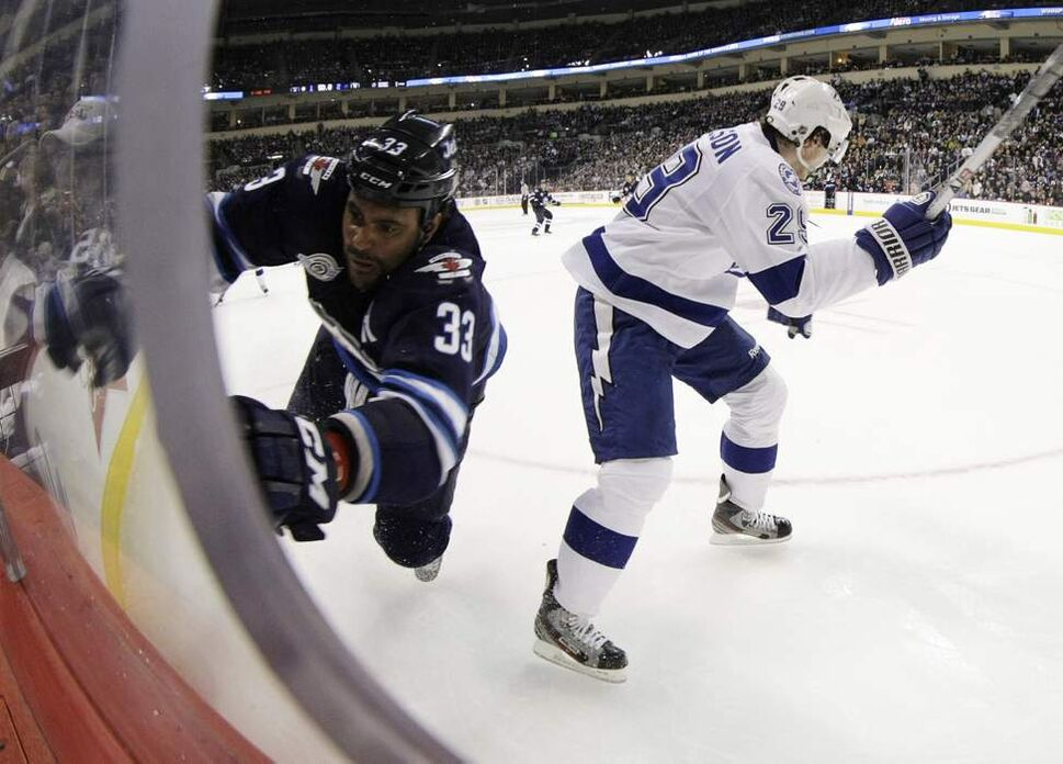 Winnipeg Jets' Dustin Byfuglien (33) is tripped up by Tampa Bay Lightning's Brendan Mikkelson (29) late in the second period of NHL action at MTS Centre in Winnipeg, Saturday, April 7, 2012. (TREVOR HAGAN/WINNIPEG FREE PRESS)