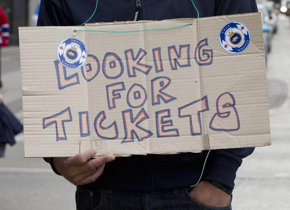A fan looks for tickets for the Jets inaugural game against the Montreal Canadiens at the MTS Centre on Sunday. (Jonathan Hayward / The Canadian Press)