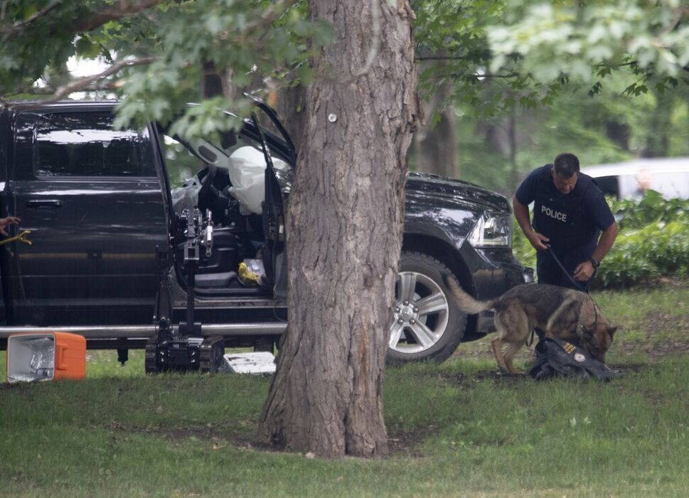 An RCMP officer works with a police dog next to a pickup truck on the grounds of Rideau Hall in Ottawa on July 2. (Adrian Wyld / The Canadian Press files) (CP)