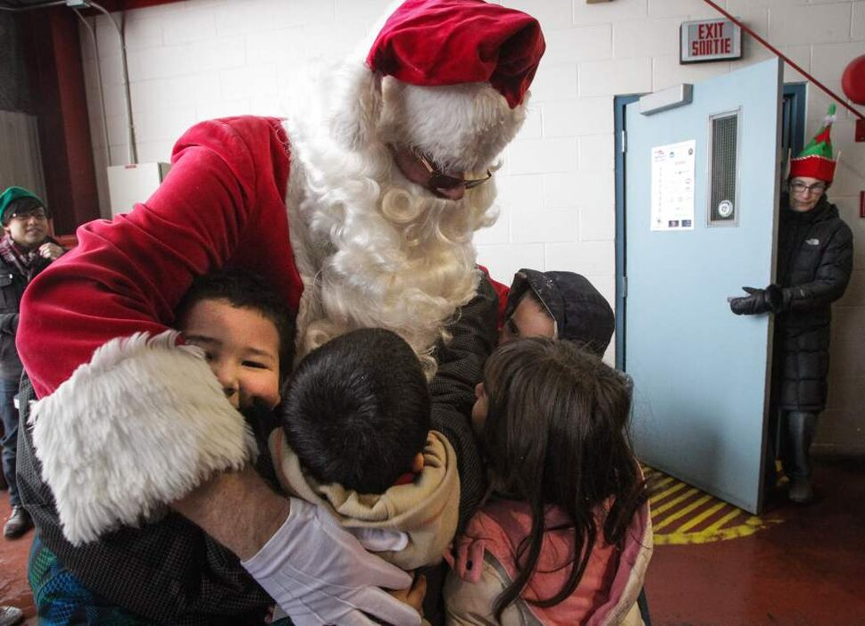 Santa gets in lots of hugs from excited school kids as he arrives after a flight on the STARS helicopter. Around 150 kids from three Winnipeg School Division elementary schools (Strathcona, Mulvey and Dufferin) got to have lunch in the Winnipeg James Armstrong Richardson International Airport's firehall, where Santa just happened to be testing out the STARS helicopter.  Monday, December 17, 2012. (MIKE DEAL / WINNIPEG FREE PRESS)