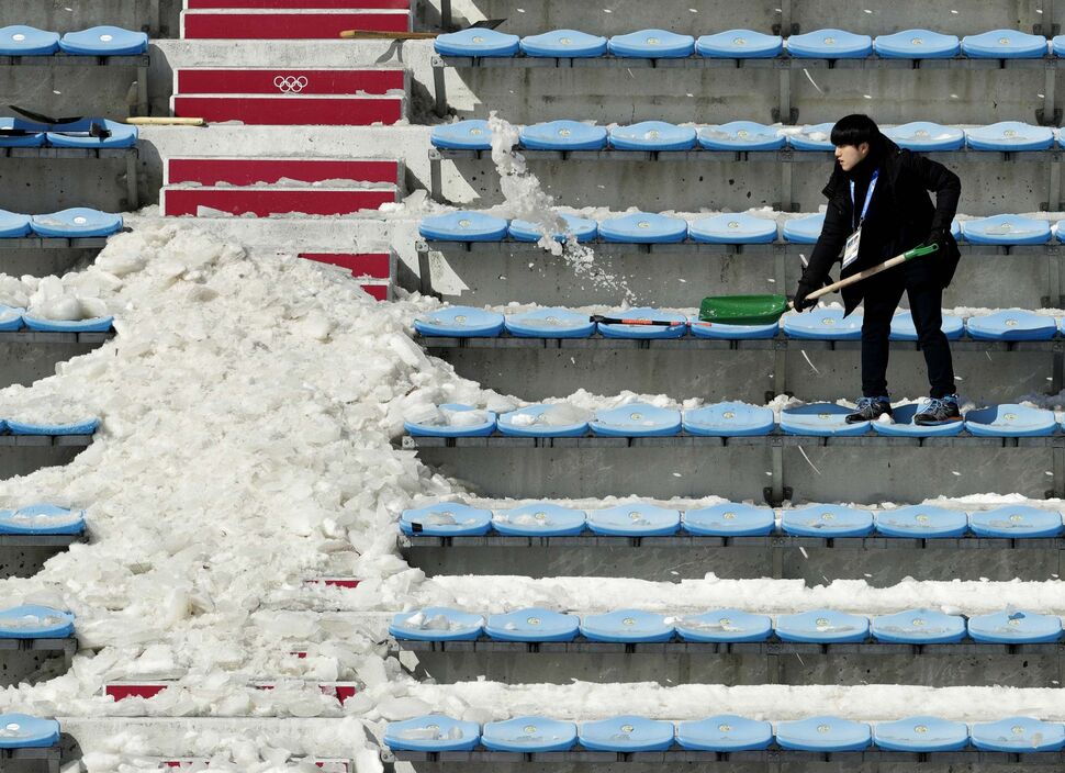 CHARLIE RIEDEL / THE ASSOCIATED PRESS</p><p>A workers shovels snow and ice from the seating area at the Alpensia Ski Jumping Center ahead of the 2018 Winter Olympics in Pyeongchang, South Korea, Wednesday, Feb. 7, 2018.</p>
