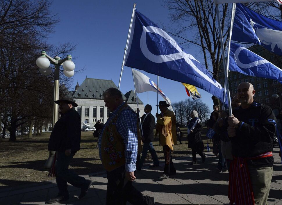 Sean Kilpatrick / The Canadian Press</p><p>David Chartrand, president of the Manitoba Metis Federation, middle, carries the Metis flag as he and fellow Metis Federation leaders and delagates march to the Supreme Court of Canada in Ottawa on Thursday.
