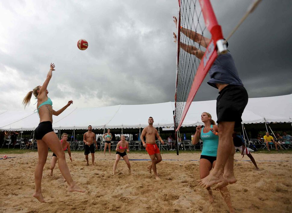 The City Kitties, left, versus Team Whiskey Dix at the Super-Spike volleyball tournament at Maple Grove Rugby Park, Friday, July 18, 2014.  (TREVOR HAGAN/WINNIPEG FREE PRESS)