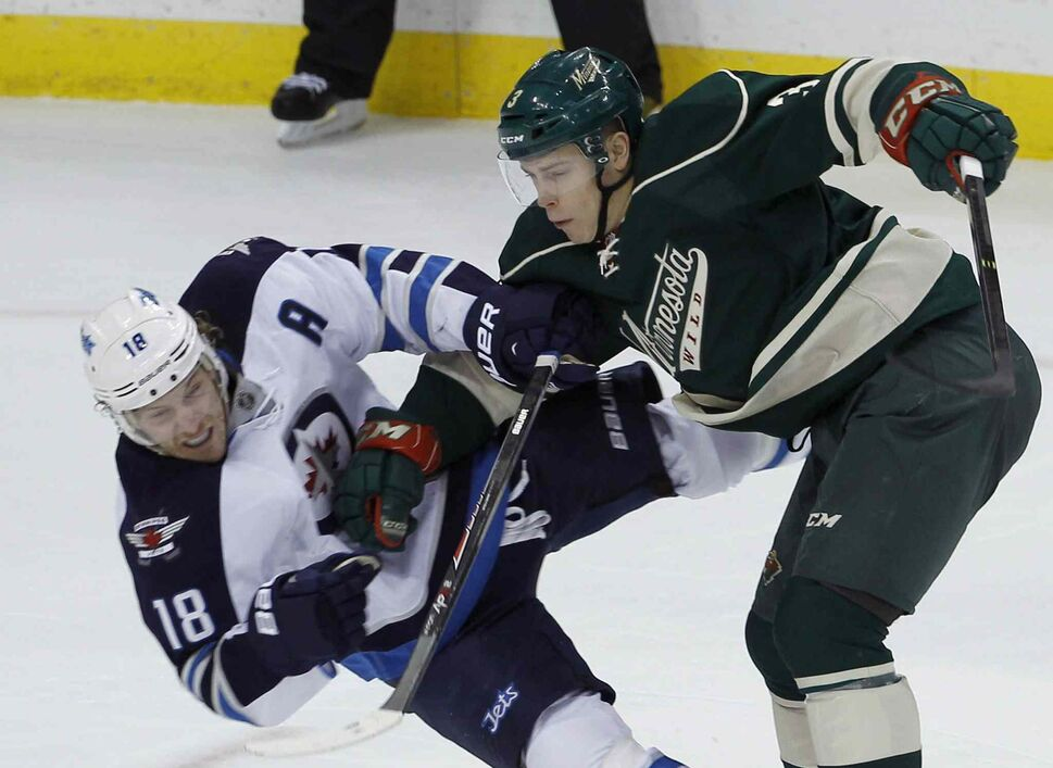 Winnipeg Jets center Bryan Little (left) takes a hit from Minnesota Wild centre Charlie Coyle during the first period. (Ann Heisenfelt / The Asociated Press)