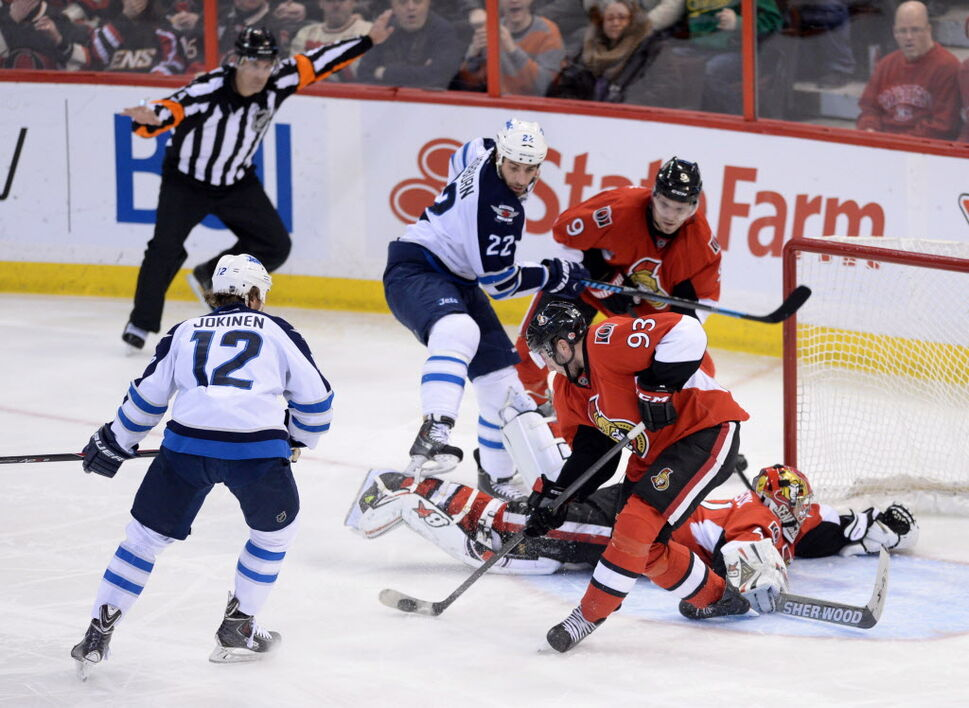 Ottawa Senators' Mika Zibanejad helps teammate Craig Anderson by making a save as Winnipeg Jets' Olli Jokinen, left, and Chris Thorburn battle it out in front of the net during the third period. The Sens defeated the Jets 4-3.  (Sean Kilpatrick / The Canadian Press)