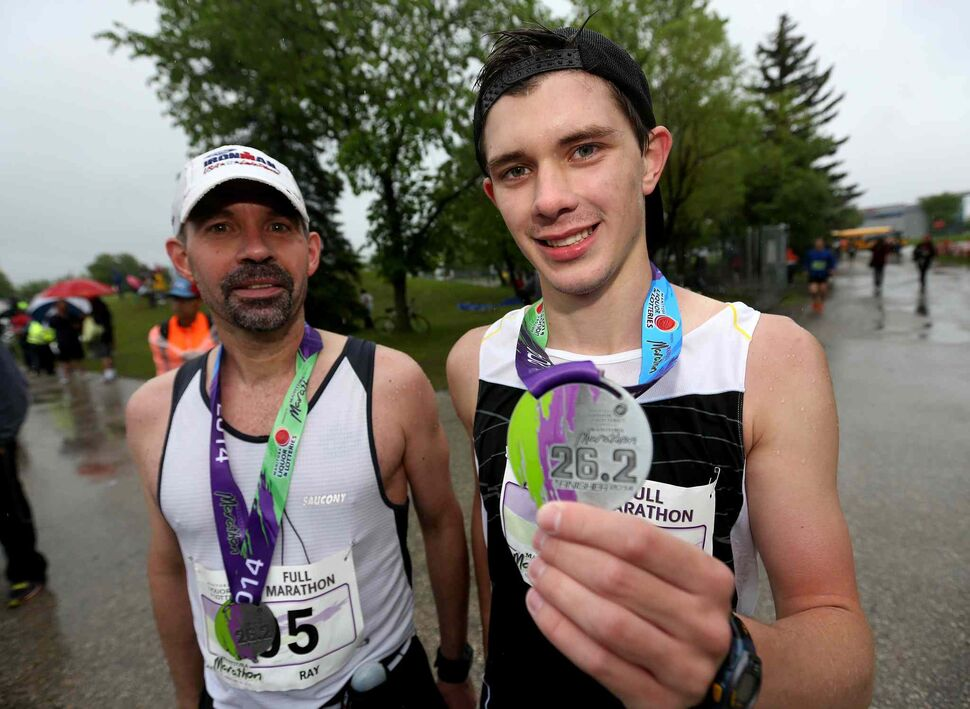 Ray McCoy and his son Kyle McCoy, 18, after completing the full marathon. (Trevor Hagan / Winnipeg Free Press)