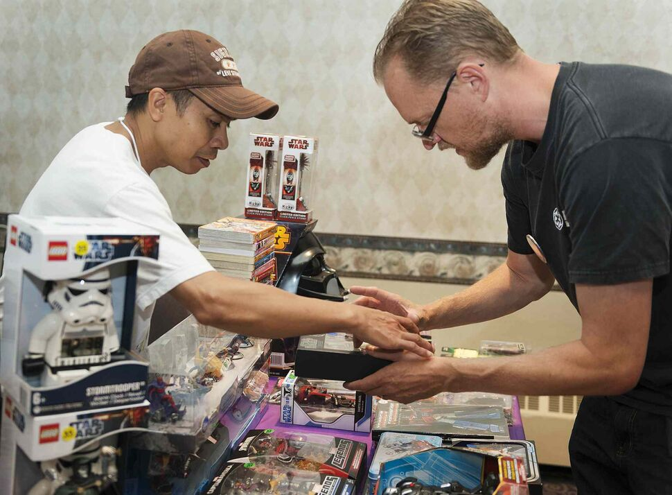 Star Wars fan Jerry Stokes (right) fit right in at Rocky Abelada's vendor in the Clarion Hotel while attending the Transformers convention with a friend on Saturday. (Sarah Taylor / Winnipeg Free Press)