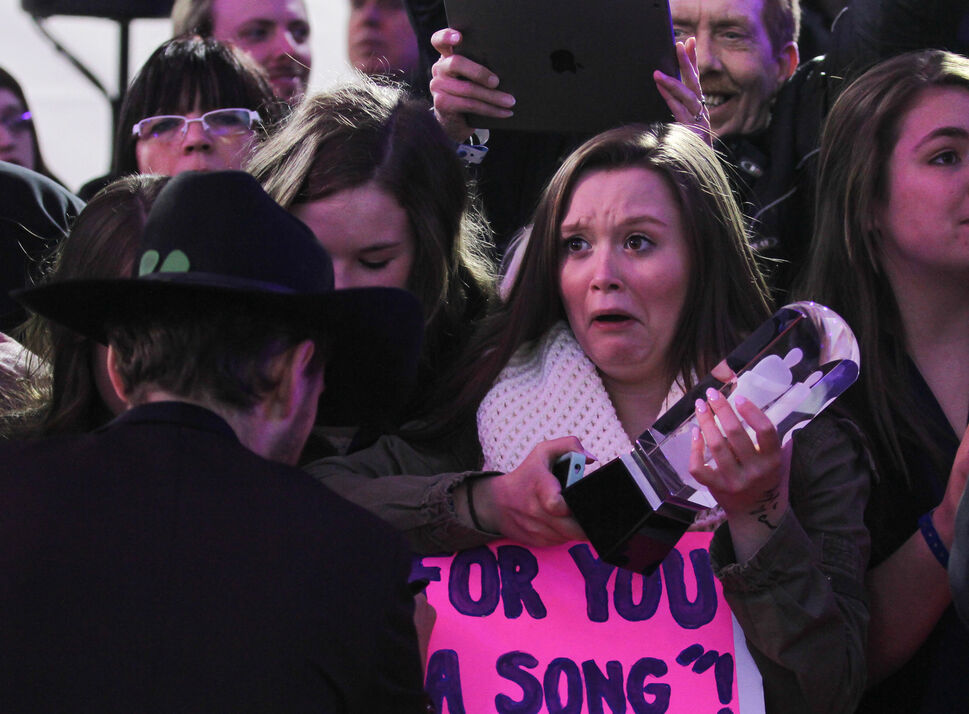 A fan reacts while holding Brett Kissel's Juno award while he signs her board on the red carpet. (Crystal Schick / Winnipeg Free Press )