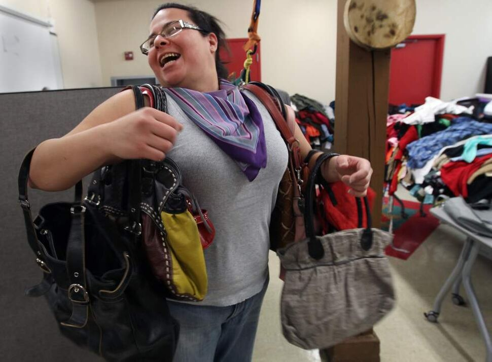 Carissa Kaminski loads up on purses and laughs with friends at the 7th annual Sister's Closet at Ka Ni Kanichihk Inc at their office at 455 McDermot Ave Thursday. The program encouraged Winnipeggers to drop off gently-used business clothing, shoes, and jewelry to support women in their goal to gain an education and move into the workforce. Ka Ni Kanichihk Inc is a community-based Aboriginal non-profit organization that helps educate and prepare women for the workforce. January 19, 2012   (JOE BRYKSA / WINNIPEG FREE PRESS)