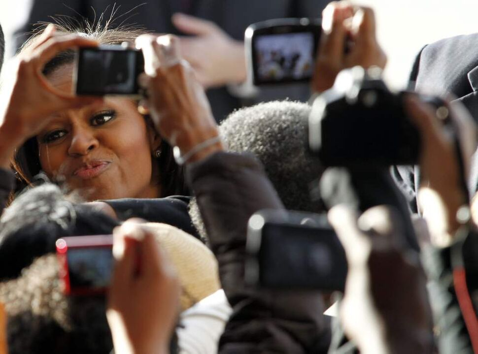 Framed by cameras and cell phones, first lady Michelle Obama thanks supporters following a rally in a hangar at the Charlotte Douglas International Airport in Charlotte, N.C., Monday, Nov. 5, 2012. (AP Photo/Bob Leverone)