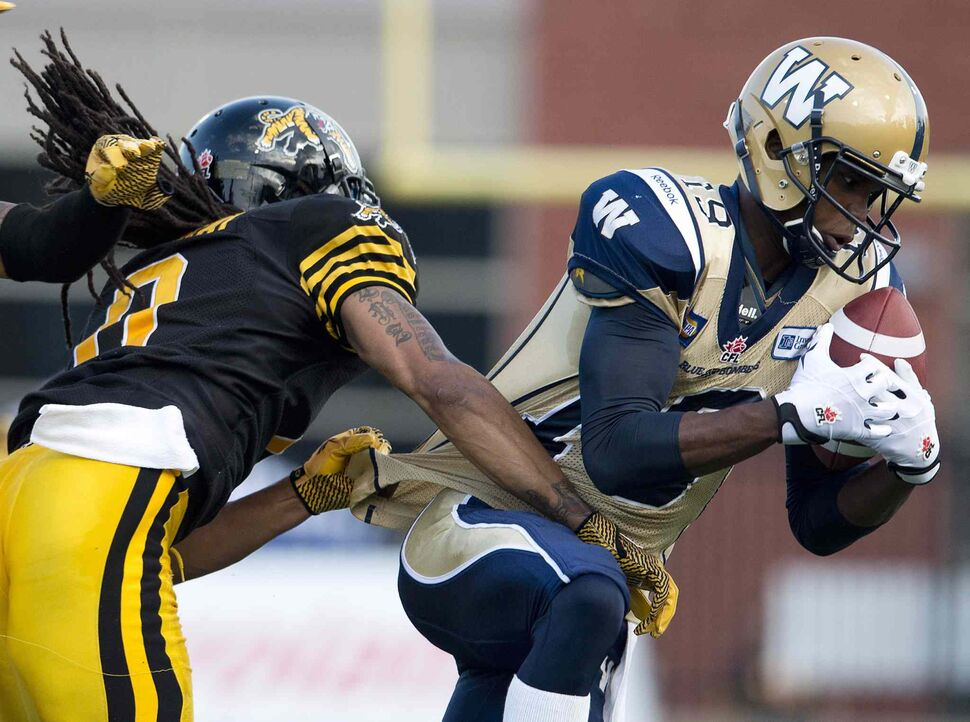 Hamilton Tiger-Cats' linebacker Rico Murray, left, tackles Winnipeg Blue Bombers' receiver Aaron Kelly, right, during the first half of Thursday's game. (Nathan Denette / The Canadian Press)