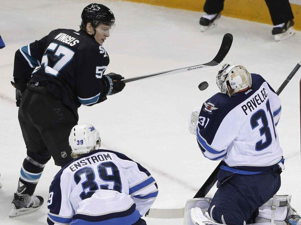Winnipeg Jets goalie Ondrej Pavelec (31), of the Czech Republic, stops a shot by San Jose Sharks' Tommy Wingels (57) during the first period of Thursday's NHL hockey game in San Jose, Calif.  (Marcio Jose Sanchez / The Associated Press)