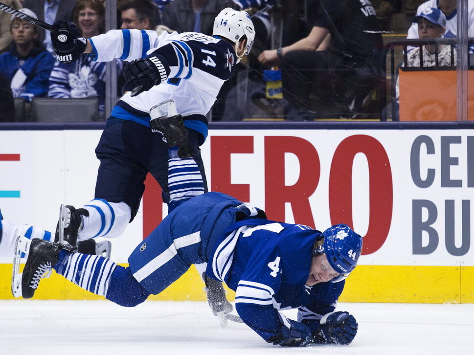 Toronto Maple Leafs defenceman Morgan Rielly, right, gets taken down by Winnipeg Jets forward Anthony Peluso, left, during first period NHL hockey action in Toronto on Saturday. (Nathan Denette / The Canadian Press)
