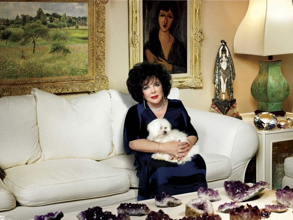Legendary actress Elizabeth Taylor poses for a photo with her dog Daisy, at her home in the Bel Air area of Los Angeles in January 2006.  (AP Photo/Harper's Bazaar, Alberto Tolot)