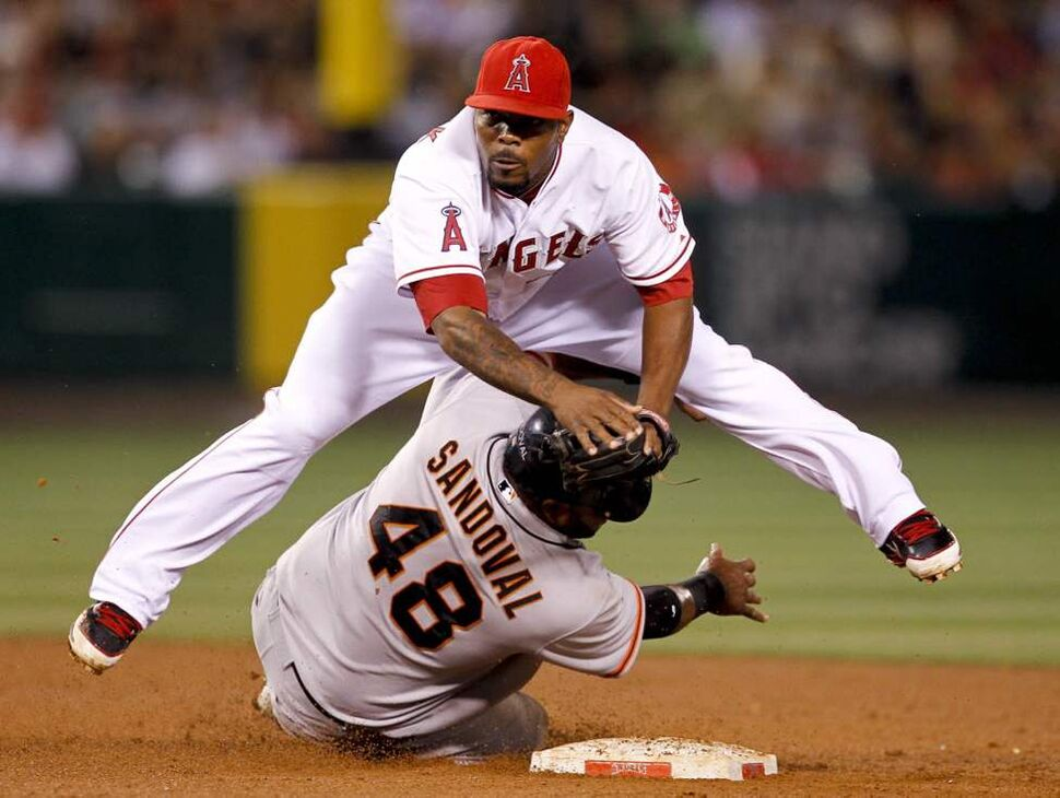 Los Angeles Angels second baseman Howard Kendrick, top, forces San Francisco Giants' Pablo Sandoval out at second and throws Hector Sanchez out at first during the sixth inning in Anaheim, Calif. (AP Photo/Chris Carlson)