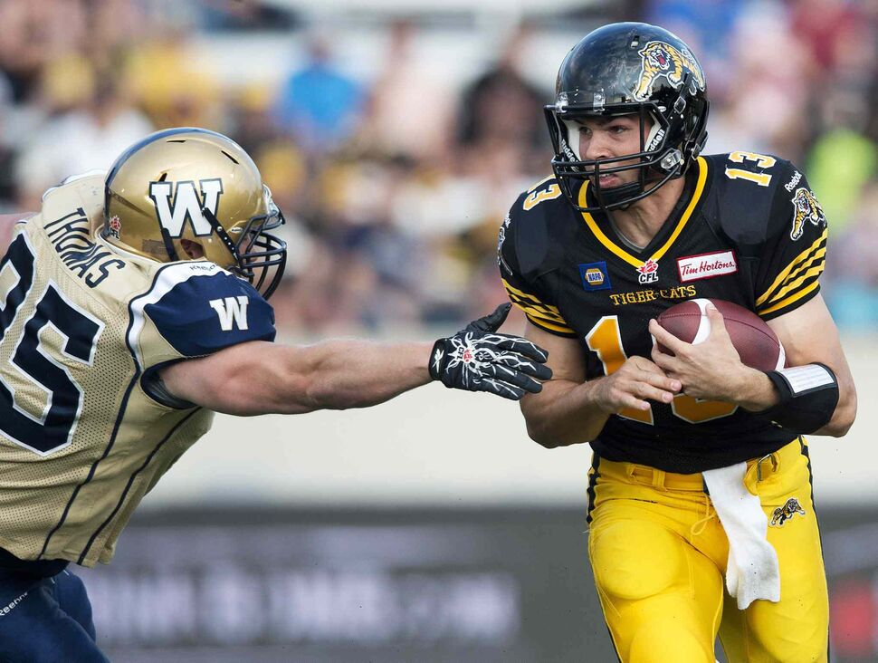 Hamilton Tiger-Cats' quarterback Dan LeFevour, right, runs the ball past Winnipeg Blue Bombers' defensive tackle Jake Thomas, left, during the first half of Thursday's game. (Nathan Denette / The Canadian Press)