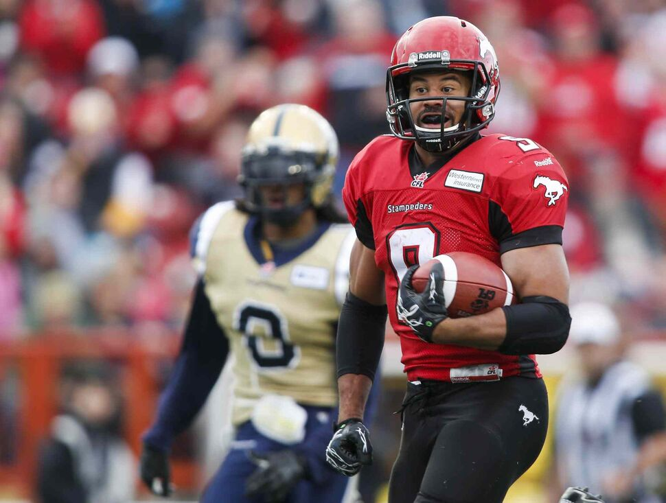 Winnipeg Blue Bombers' Johnny Sears Jr. looks on as Calgary Stampeders' Jon Cornish smiles after scoring a touchdown during the first half. (Jeff McIntosh / The Canadian Press)
